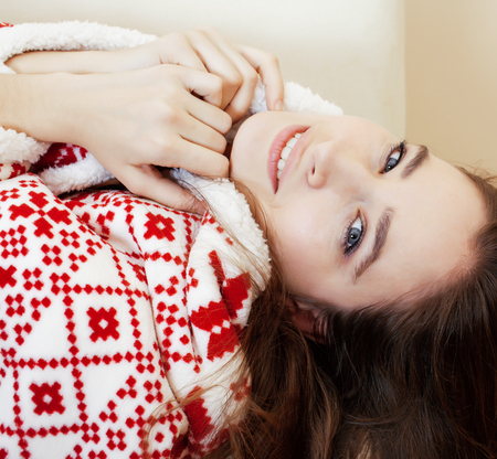an adult person: young pretty brunette girl in Christmas ornament blanket getting warm on cold winter, freshness beauty concept close up Stock Photo