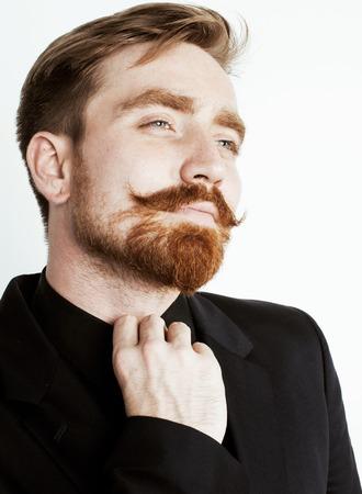 hombres guapos: joven hombre de pelo rojo con barba y bigote en traje negro sobre fondo blanco de cerca