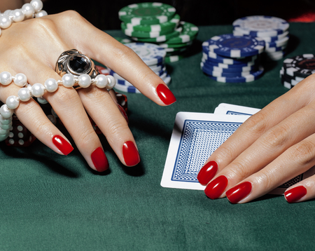 looser: hands of young caucasian woman with red manicure at casino green table close up, luxury jewelry