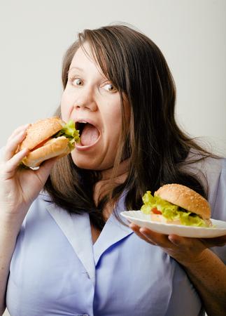 mujeres gordas: mujer blanca grasa que tiene posibilidad de elegir entre la hamburguesa y ensalada de cerca, el concepto de alimentos poco saludables