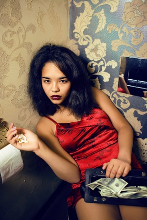 prostitute: pretty young african american woman in luxury restroom with money, like prostitute, dirty cash concept