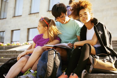 multy: cute group of teenages at the building of university with books huggings, diversity nations, back to school