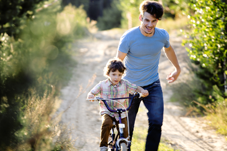 enjoing: father learning his son to ride on bicycle outside, real happy family in summer forest enjoing nature warm air