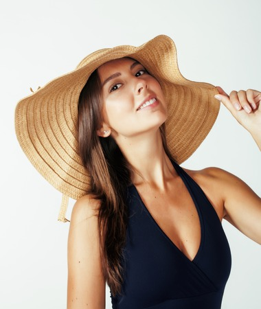 summer beauty: young pretty brunette woman wearing summer hat and swimsuit isolated on white background preparing to vacations, smiling emotional posing, lifestyle concept Stock Photo