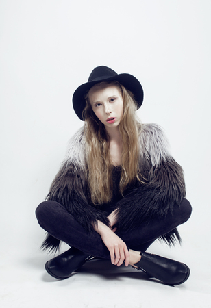 blonde teenage girl: young blonde teenage girl in hat and fur coat, fashion dressed model, studio shot, modern lifestyle concept