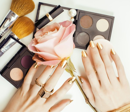 woman hands with golden manicure and many rings holding brushes, makeup artist stuff stylish, pure close up pink flower rose tenderness among cosmetic
