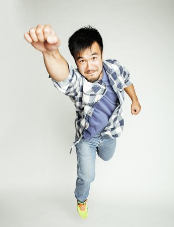 ジャンプ白い背景、ライフ スタイルの人々 の概念、supeman 飛行に対する陽気な若いかなりアジア男
