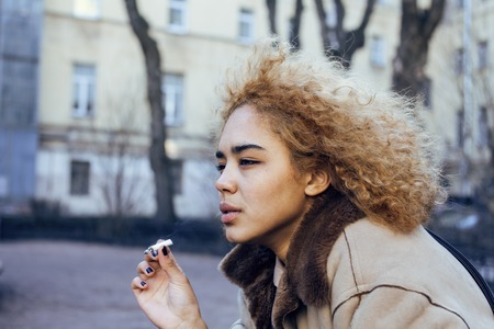 bad skin: young pretty girl teenage outside smoking cigarette close up, looking like real junky, social issues concept Stock Photo