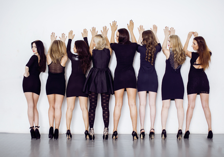 squad: Many diverse women in line, wearing fancy little black dresses, party makeup, vice squad concept hot Stock Photo
