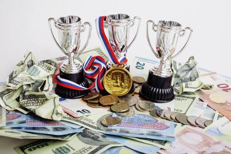 primer lugar: Deporte concepto ganador: tres tazas entre las monedas diversa euro, dólar, rubl, medalla de oro en primer lugar se cierran para arriba