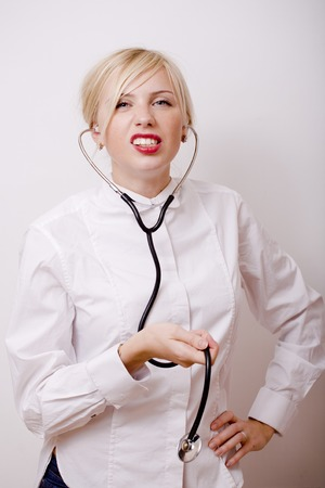 wearied: funny doctor with stethoscope, smiling blond woman medical equipment showing on white background, real people lifestyle