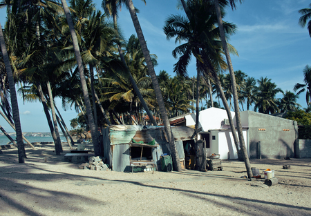 destructed: little vietnamese house on seacoast among palms and sand, poor fisherman home