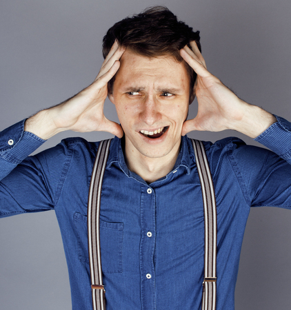 pimples: young goofy man with pimples pointing in studio, stupid bookwarm little crazy Stock Photo