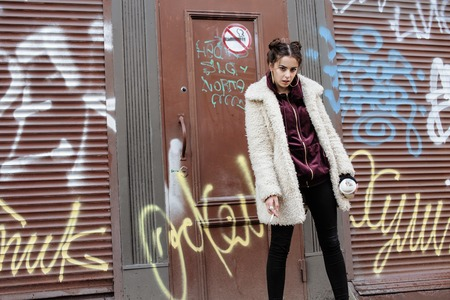 junky: young pretty stylish teenage girl outside in city wall with graffity smoking cigarette at forbidden smoke sighn, lifestyle concept