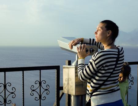 mujer mirando el horizonte: joven mujer de verdad mirando a trav�s de telescopio en el punto de vista del mar en el parque Ataturk, ma�ana soleada, la gente de estilo de vida concepto