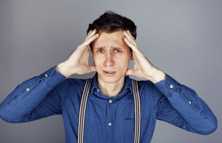 goofy: young goofy man with pimples pointing in studio, stupid bookwarm little crazy Stock Photo