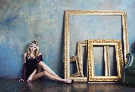 heir: young blond woman wearing crown in fairy luxury interior with empty antique frames total wealth sexual close up