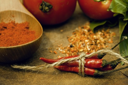 ferm: vegetables on wooden kitchen with spicies, tomato, chilli, green beans, garlic close up blurred background