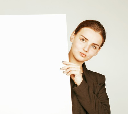 business costume: young pretty brunette girl with placard shit copyspace on white background wearing business costume student Stock Photo