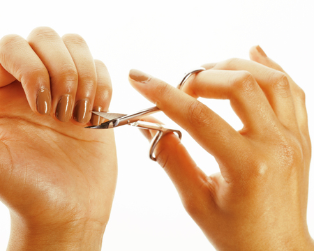 depraved: african american woman hands making no qualified manicure, pedicure to herself isolated with tools, bad nails concept Stock Photo