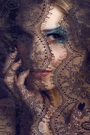 mistery: portrait of beauty young woman through lace close up mistery makeup, stylish fashion lady