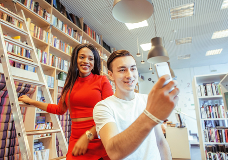 univercity: couple students in univercity library, looking book, preparing to exam, having fun, making selfie, lifestyle people concept
