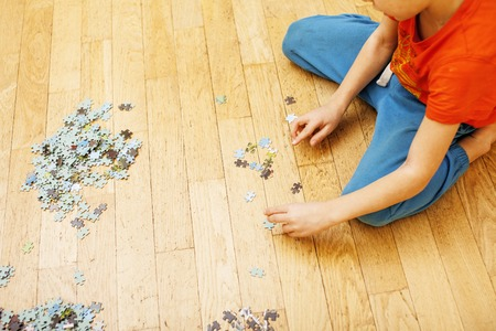 little kid playing with puzzles on wooden floor together with parent, lifestyle people concept, loving hands to each other, warm wooden interior Standard-Bild