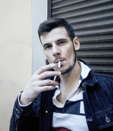 ruffian: middle age man smoking cigarette on backjard, real stylish tough guy, lifestyle people concept