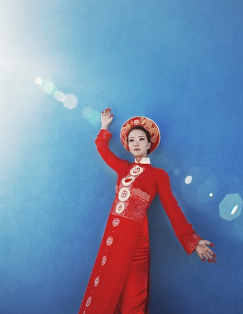 normal school: beauty young vietnamese woman in red national ethnic costume, real cheerful girl on blue background