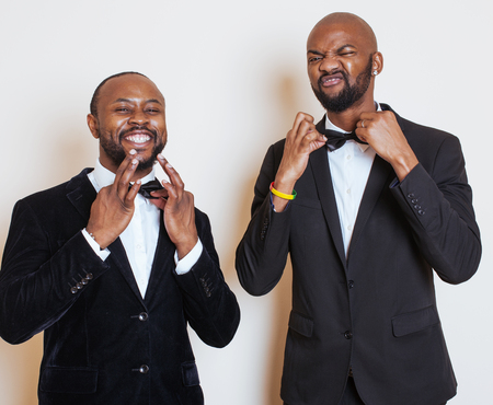 african business man: two afro-american businessmen in black suits emotional posing, gesturing, smiling. wearing bow-ties, lifestyle people concept