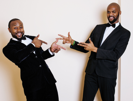 dinky: two afro-american businessmen in black suits emotional posing, gesturing, smiling. wearing bow-ties, lifestyle people concept
