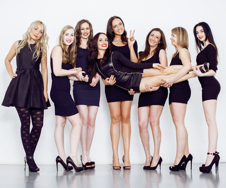 Many diverse women in line, wearing fancy little black dresses, party makeup, vice squad concept lifestyle Stock Photo