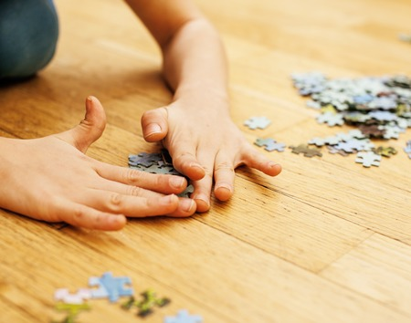 loving hands: little kid playing with puzzles on wooden floor together with parent, lifestyle people concept, loving hands to each other close up