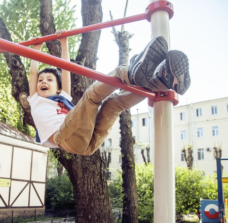 little cute blond boy hanging on playground outside, alone training with fun, lifestyle children concept, summer vacations