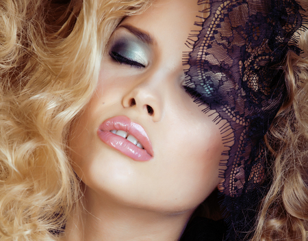 seduction: Portrait of beauty blond young woman through black lace close up sensual seduction makeup
