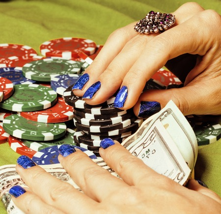 poker card: hands of young caucasian woman with red manicure at casino green table close up, luxury jewelry