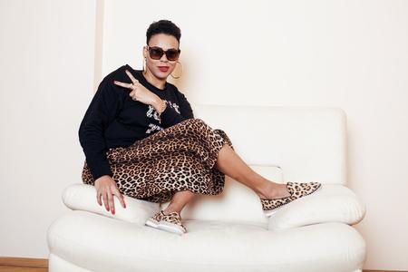 donna ricca: piuttosto afroamericano alla moda donna Big Mama ben vestito. malloppo rilassarsi a casa, Pelle di leopardo su clothers. occhiali da sole sguardo di moda Archivio Fotografico
