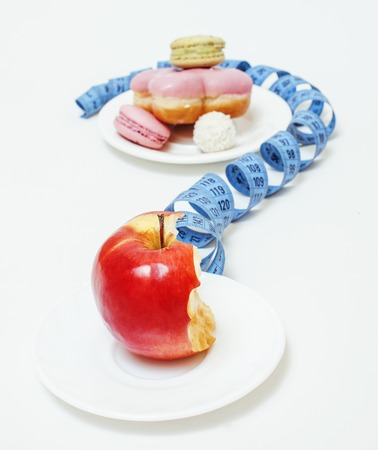 donut shape: new diet concept, question sign in shape of measurment tape between red apple and donut isolated on white