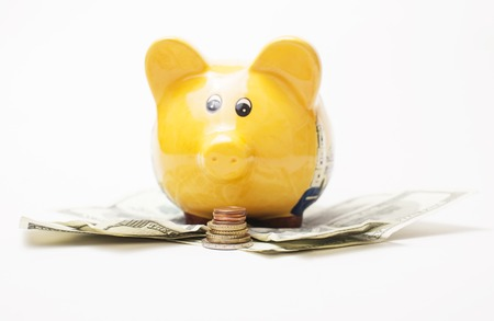 savety: Yellow piggy bank and Stack of money coins isolated over the white background lot of dollar cash under it, savety concept Stock Photo