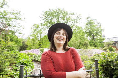 mature brunette: mature brunette fat woman in green garden wearing hat, smiling, friendly welkoming, lifestyle people concept close up