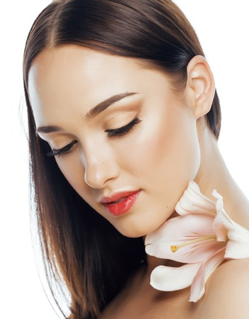 spa flower: young attractive lady close up with hands on face isolated flower lily brunette spa nude makeup, beautiful woman