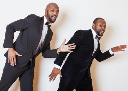 dinky: two afro-american businessmen in black suits emotional posing, gesturing, smiling. wearing bow-ties joking