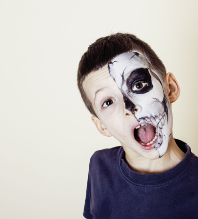 little cute boy with facepaint like skeleton to celebrate halloween, emotional kid