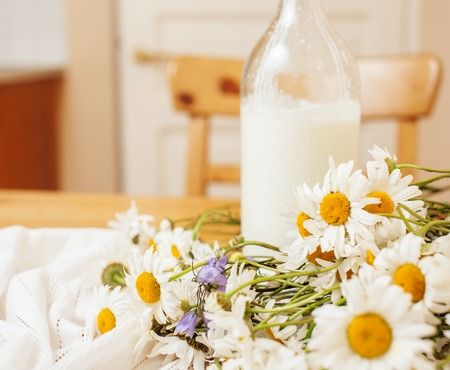 simply: Simply stylish wooden kitchen with bottle of milk and glass on table, summer flowers camomile, healthy food moring concept close up Stock Photo