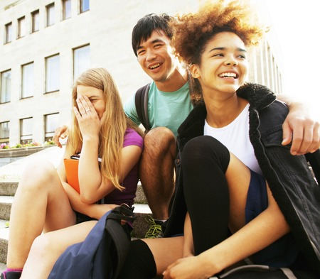 multy: cute group of teenages at the building of university with books huggings