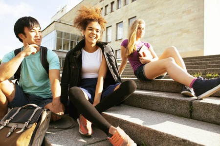 multy: cute group of teenages at the building of university with books huggings, back to school Stock Photo