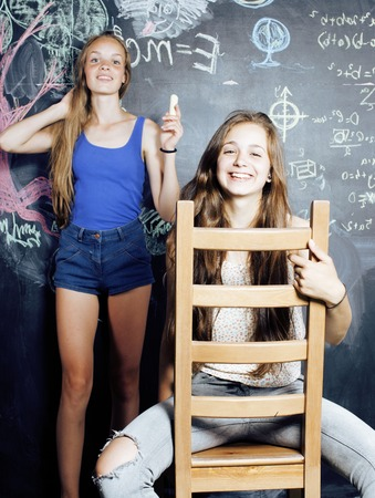normal school: back to school after summer vacations, two teen real girls in classroom with blackboard painted together close up