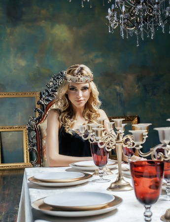 heir: young blond woman wearing crown in fairy luxury interior with empty antique frames total wealth close up