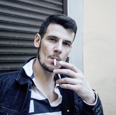 tough guy: middle age man smoking cigarette on backjard, stylish tough guy, lifestyle people concept close up