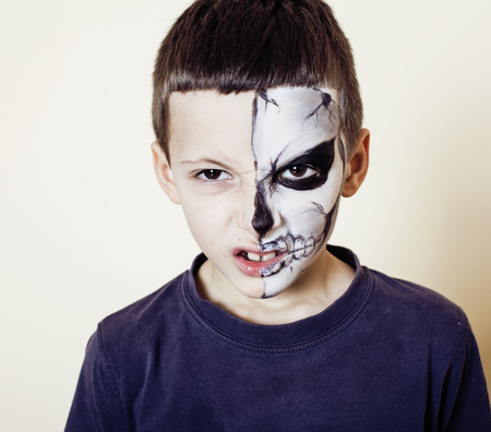 young adult man: little cute boy with facepaint like skeleton to celebrate halloween emotional posing on white background Stock Photo